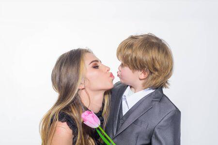Regalo de cumpleaños. Lindo hijo felicita a la madre por el cumpleaños. El hermano le da a la hermana una flor de tulipán. Celebración del día de la mujer. El hijo le da a mamá una flor para las vacaciones. Día de la Madre. Pequeño hijo y madre felices juntos