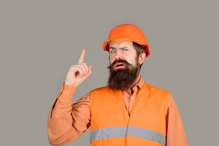 Man builder having good idea. Builder in protective clothing and helmet. Engineer warns of danger lifting his finger up. Man builder in hard hat shows warning sign with finger. Builder in hardhat