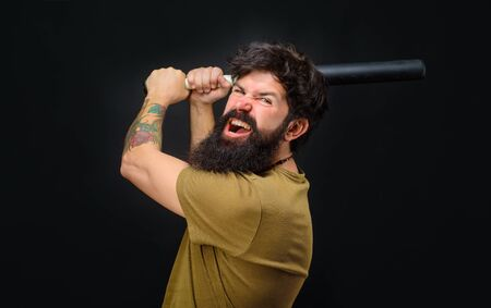 Baseball player with baseball bat. Angry man in t-shirt ready to swing. Sports and baseball training. Sport equipment. Sport, training, health. Power and energy concept. Bearded man with baseball bat