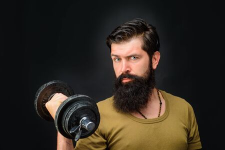 Fitness. Sportsman with dumbbells training. Sportsman making weightlifting. Lose weight. Strong man training with dumbbells. Bearded man exercise with dumbbells. Handsome athlete man with dumbbells Stock Photo