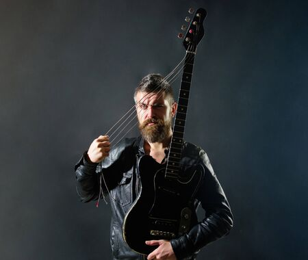 Music party. Sexy guitarist with musical instrument. Handsome rock star in leather jacket. Music concept. Bearded man with electric guitar. Guitarist with bass guitar. Musician holds electric guitar 版權商用圖片