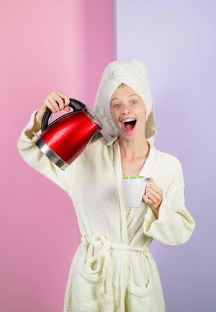 Jolie fille verse de l'eau chaude de la bouilloire dans la cuisine. Fille faisant du thé. Une femme souriante verse de l'eau de la bouilloire dans la tasse. Fille verse de l'eau dans une tasse de bouilloire électrique. Femme au foyer heureuse en peignoir à la maison