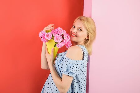 Young woman holds flower bouquet. Happy emotional woman holds flowers. Beautiful girl in trendy dress with flowers in hands. Sexy woman with makeup holds bouquet of roses. Smiling girl with bouquet