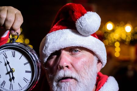 Christmas clock. New year clock. Time to celebrate. Merry Christmas. Happy new year. Christmas time. Santa man celebrate Christmas. New year party. Winter holidays. Santa Claus man holds alarm clock Stock Photo