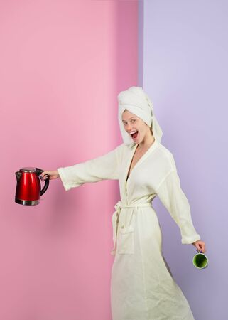 Good morning. Female housewife with electric kettle in kitchen. Breakfast. Girl with electric kettle and cup. Happy housewife holds tea kettle and mug. Beautiful woman in bathrobe and towel on head