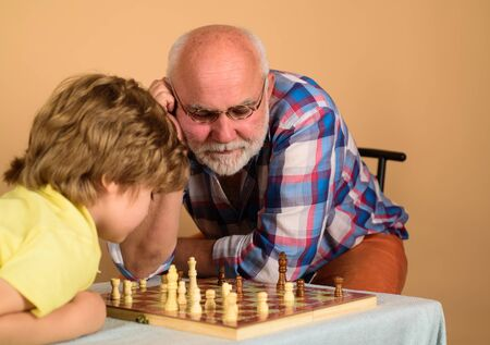Family relationship with grandfather and grandson. Game of chess. Child playing chess with grandpa. Senior man thinking about his next move in game of chess. Grandfather teaching grandson play chess