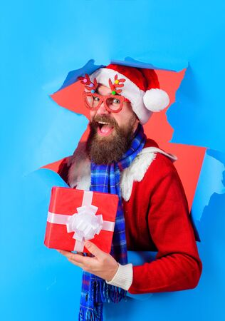 Christmas present. Happy Santa Claus man holds gift box. Holiday poster design, banner. Smiling Santa in party glasses looking through hole in paper. New year, winter. Discount, sale, season sales