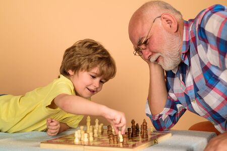 Kid boy playing chess with grandfather. Chess competition. Grandfather and grandson playing chess. Grandpa and grandson playing chess spending free time together. Brain development and logic concept