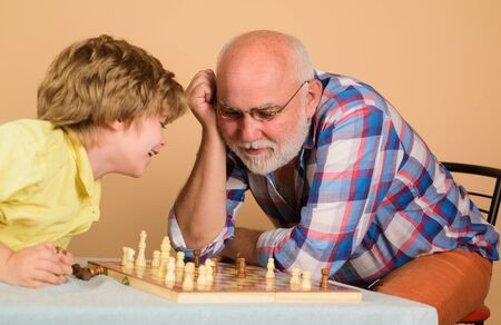 Grandpa teaching his grandson to play chess. Senior man thinking about his next move in game of chess. Grandfather and grandson playing chess. Childhood and board game. Child playing intelligent game