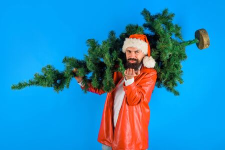 Bearded man in Santa Claus costume holds Christmas tree and send kiss. Christmas. Santa man holds christmas tree. Pine tree. Santa man with fir-tree. Santa send kiss. Christmas, new year, holiday Standard-Bild