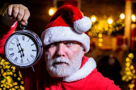 Christmas clock. Time to celebrate. Merry Christmas. Happy new year. Christmas time. Santa man celebrate Christmas. New year party. New year clock. Winter holidays. Santa Claus man holds alarm clock