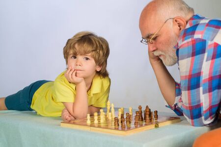 Grandfather and grandson playing chess. Childhood and board game. Child playing intelligent game. Grandpa teaching his grandson to play chess. Senior man thinking about his next move in game of chess