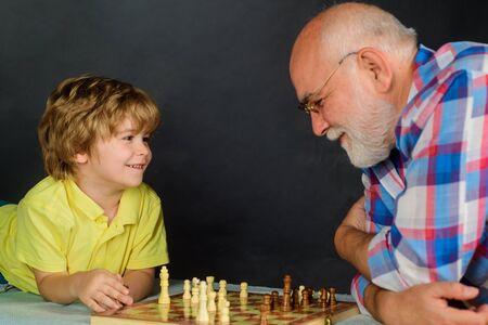 Grootvader en kleinzoon schaken. Opa leert zijn kleinzoon schaken. Kind dat intelligent spel speelt. Senior man denken over zijn volgende zet in schaakspel. Jeugd- en bordspel