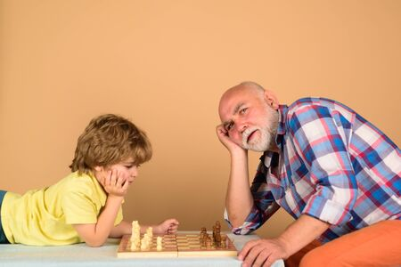 Grandfather and grandson playing chess. Child boy playing chess with grandfather. Little boy think or plan chess game. Little boy learning to play chess. Checkmate. Games and activities for children
