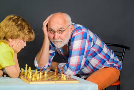 Little boy playing chess with grandpa. Childhood and board games. Brain development and logic concept. Cute boy developing chess strategy. Chess competition. Grandfather and grandson playing chess Фото со стока - 136595337