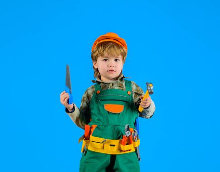 Little boy with helmet and tools. Little repairman. Kid as construction worker. Little boy in builder's uniform with tools. Little boy plays construction worker. Builder. Kid game. Tools for building Banque d'images