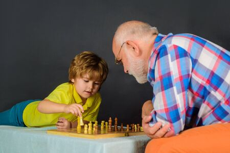 Little boy learning to play chess. Games and activities for children. Grandfather and grandson playing chess. Child boy playing chess with grandfather. Little boy think or plan chess game. Checkmate