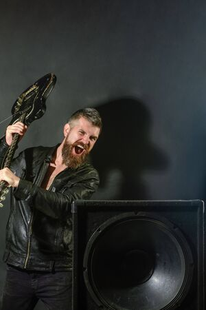 Guitarist breaks guitar at music column. Angry man with beard breaks guitar at music speakers. Emotions, aggression, musical instruments. Guitar player at rock concert. Musician with electric guitar Reklamní fotografie