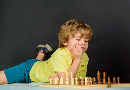 Cute little boy playing chess enjoying leisure time. Smart kid playing chess thinking how to make move. Child playing intelligent game. Chessman. Cute little boy playing chess at home. Chess match