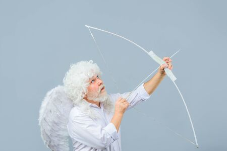 Happy Valentine's Day. February 14. Cupid shoot with bow. Valentines day angel. Man in angel costume. Cupid. Amour. God of Love. Concept of Valentines Day Stock fotó