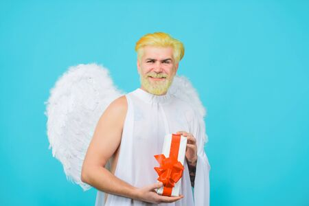 Concept of Valentines Day. Happy Valentine's Day. February 14. Cupid with gift. Valentines day. Smiling blonde man in angel costume holds present.