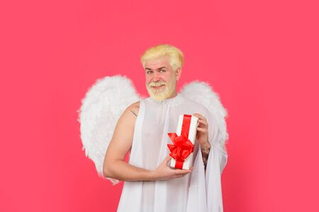 Happy Valentine's Day. February 14. Cupid with gift. Valentines day. Smiling blonde man in angel costume holds present. Cupid. Amour. God of Love. Concept of Valentines Day