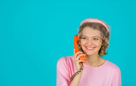 Smiling woman in pink dress with telephone handset. Happy woman holds handset. Pretty woman talking at retro handset. Girl talking on landline phone. Communication. Young woman talking on retro phone Фото со стока