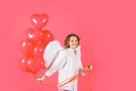 Happy Valentine's Day. Valentines day angel. Curly blonde woman in angel costume. Cupid. Amour. Cupid with heart shaped balloons.