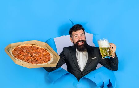 Pizza time. Fastfood. Italian food. Satisfied man with beard and mustache enjoy delicious pizza and cold beer. Pizza delivery concept. Bearded man with tasty pizza and beer looking through paper hole Standard-Bild
