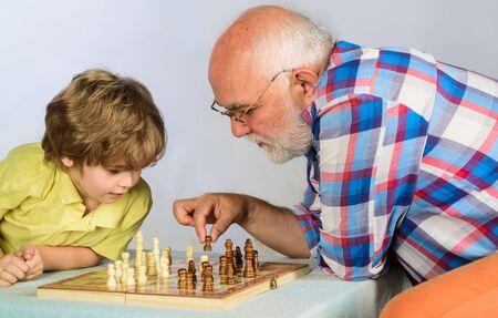 Schachwettbewerb. Kindheit und Brettspiele. Großvater und Enkel spielen Schach. Kleiner Junge, der mit Opa Schach spielt. Gehirnentwicklung und Logikkonzept. Netter Junge entwickelt Schachstrategie