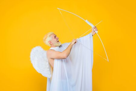 Happy Valentine's Day. Valentines day angel. Smiling blonde man in angel costume. Cupid. Amour. Cupid with bow. God of Love. Concept of Valentines Day Stock fotó