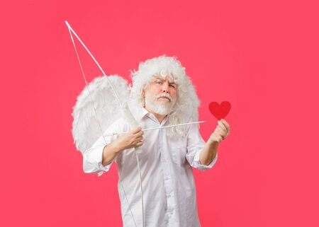Handsome Cupid. Valentines Day. Angel man with white wings. Love concept. Valentine angel. Bearded man with angel wings. Valentines day card. Cupid holds valnetines heart. Valentines cupid
