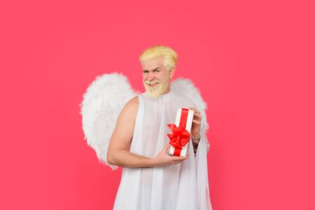 Valentines day. Cupid with gift. Love concept. Cupid. Smiling man in angel costume. February 14. Cupid with gift box. Valentine angel. Cupid angel with present box. Happy Valentines Day. Amour