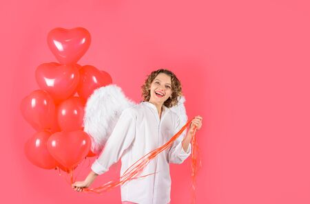 Love story concept. Female angel. Cupid with heart shaped balloons. Happy woman with angel wings holds heart balloons. Valentines day. St. Valentine day. Sexy woman dressed as angel with red balloons Standard-Bild - 137750489