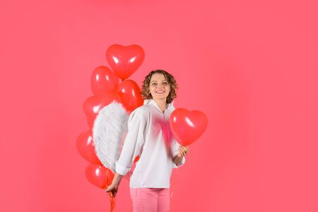 Love story concept. Sexy woman dressed as angel with red balloons. Female angel. Cupid with heart shaped balloons. Happy woman with angel wings holds heart balloons. Valentines day. St. Valentine day