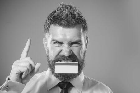 Businessman holds credit card in mouth pointing finger up. Cashless payment. Banking service. Business idea concept. Bank-card with magnetic stripe. Plastic bank-card design mock up with magstripe