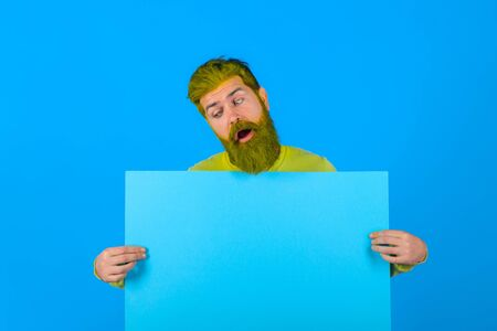 Surprised bearded man holding advertising board. Advertising and sale. Online shopping. Advertising banner. Seasons sale. Discount. Marketing. Add. Copy space for text. Sellout
