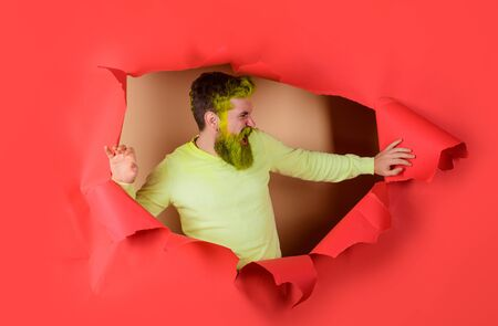 Screaming man in yellow sweater looking through hole. Fashionable man with dyed hair and beard. Advertising. Discount, sale. Angry man looking through hole in paper. Bearded man making hole in paper