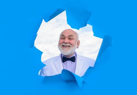Happy old bearded man through hole in blue paper. Man in suit.Through paper. Advertising. Happy. Emotions. Smiling. Discount, sale, season sales. Man through paper