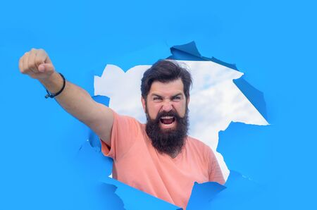 Screaming bearded man through hole in paper.Through paper. Victory. Advertising. Happy. Emotions. Smiling. Discount. Sale. Season sales. Sellout. Man through paper