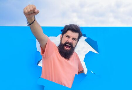 Happy bearded man through hole in blue paper. Win. Through paper. Advertising. Happy. Emotions. Smiling. Discount. Sale. Season sales. Man through paper. Victory Stok Fotoğraf