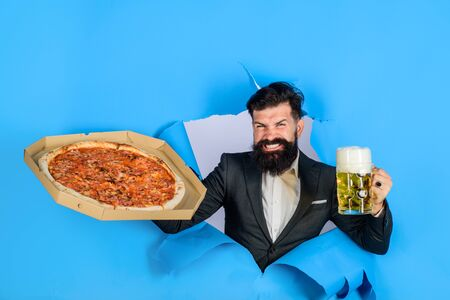 Pizza delivery concept. Bearded man with tasty pizza and beer looking through paper hole. Pizza time. Fastfood. Italian food. Satisfied man with beard and mustache enjoy delicious pizza and cold beer Stok Fotoğraf