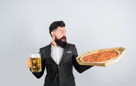 Pizza time. Surprised man with beard holds delicious pizza in box and cold beer. Pizza delivery concept. Fastfood. Italian food. Bearded man with tasty pizza and beer in hands. Restaurant or pizzeria Stok Fotoğraf