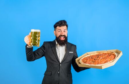 Restaurant or pizzeria. Fast food. Italian food. Bearded man with tasty pizza and beer in hands. Pizza time. Smiling man with beard holds delicious pizza in box and cold beer. Pizza delivery concept Stok Fotoğraf