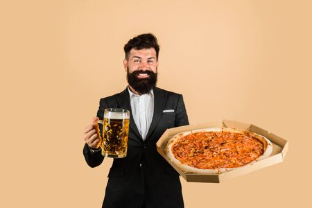 Restaurant or pizzeria. Smiling man with beard holds delicious pizza in box and cold beer. Fast food. Italian food. Bearded man with tasty pizza and beer in hands. Pizza time. Pizza delivery concept Archivio Fotografico