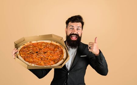 Pizza delivery concept. Businessman with pizza in box shows thumb up. Taste delicious fastfood. Businessman holds pizza. Delicious italian pizza in box. Bearded man in suit. Food, business lunch Stok Fotoğraf