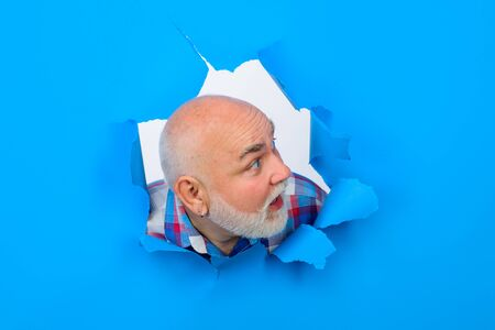 Surprised old bearded man through hole in blue paper. Through paper. Advertising. Happy. Emotions. Smiling. Discount, sale, season sales. Man looking to the right