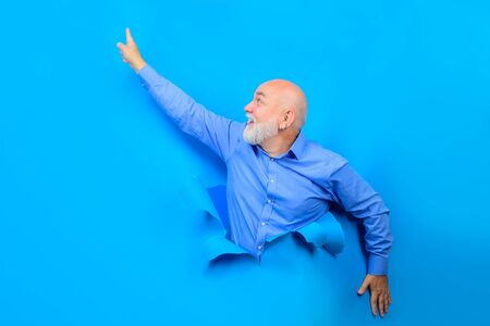 Smiling old bearded man through hole in blue paper. Old man points up. Copy space for advertising. Discount, sale, season sales. Through paper. Advertising