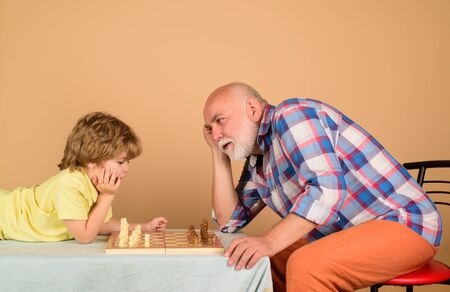 Chess competition. Cute boy developing chess strategy. Childhood and board games. Grandfather and grandson playing chess. Little boy playing chess with grandpa. Brain development and logic concept Stok Fotoğraf