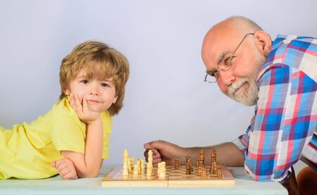 Childhood and board games. Chess competition. Little boy playing chess with grandpa. Cute boy developing chess strategy. Grandfather and grandson playing chess. Brain development and logic concept